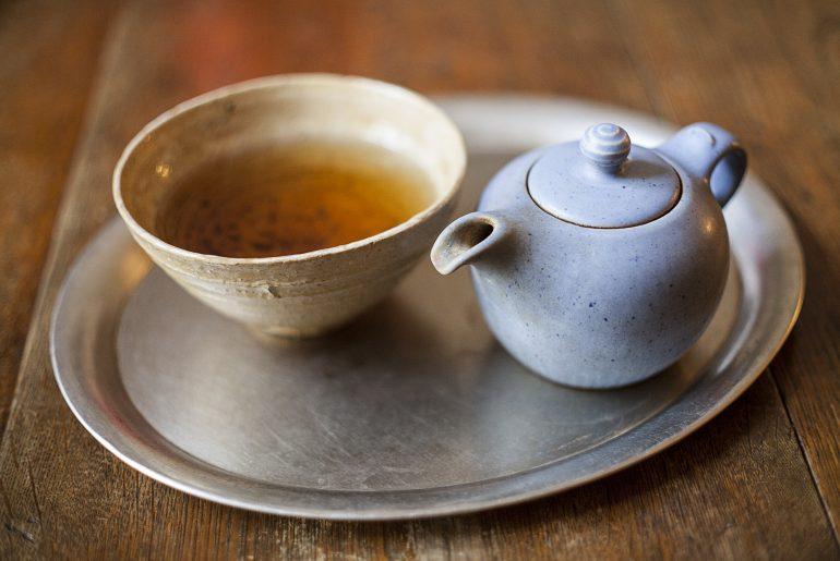 Na podanej przez kelnerkę tacy znajduje się herbata oolong, morze herbaty oraz stylowy czajniczek w którym parzona jest herbata turkusowa.