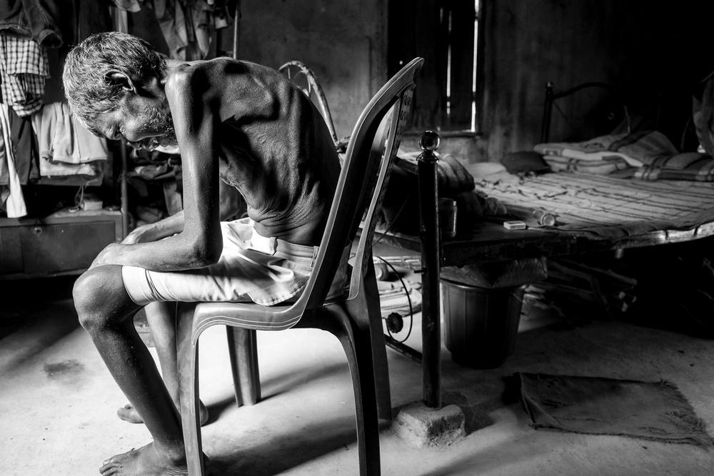 Niedożywiony, schorowany człowiek, czeka na syna siedząc na plastikowym krześle.