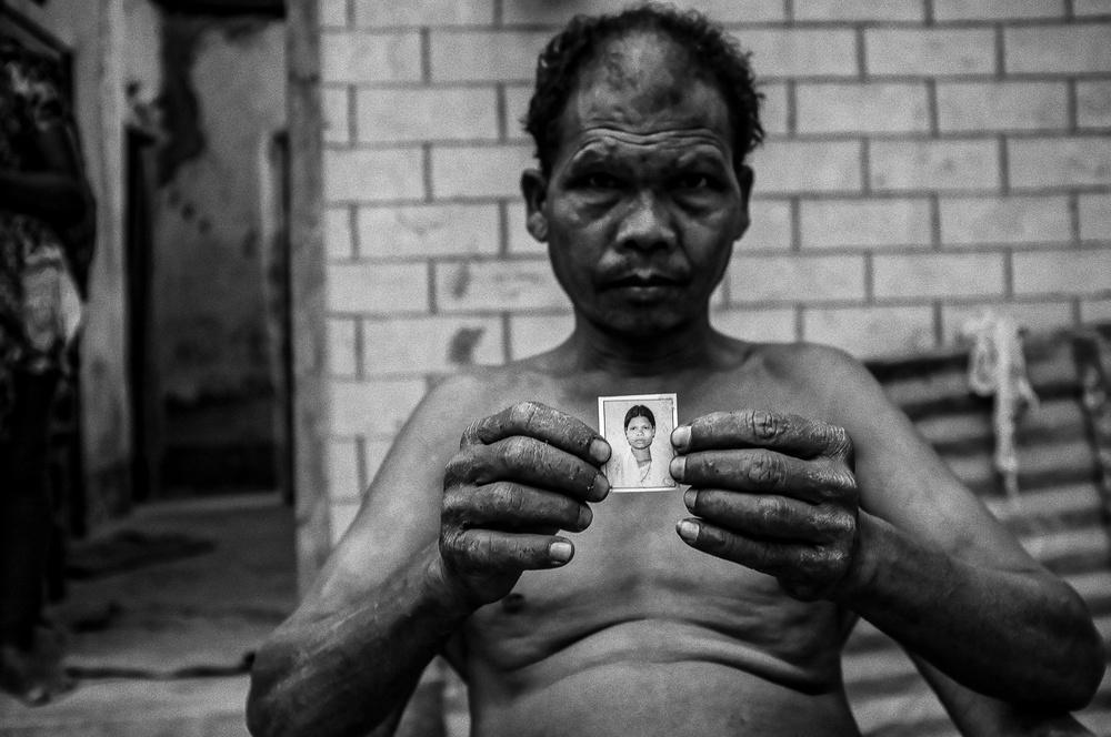 Mężczyzna pokazuje zdjęcie córki, która została uprowadzona.