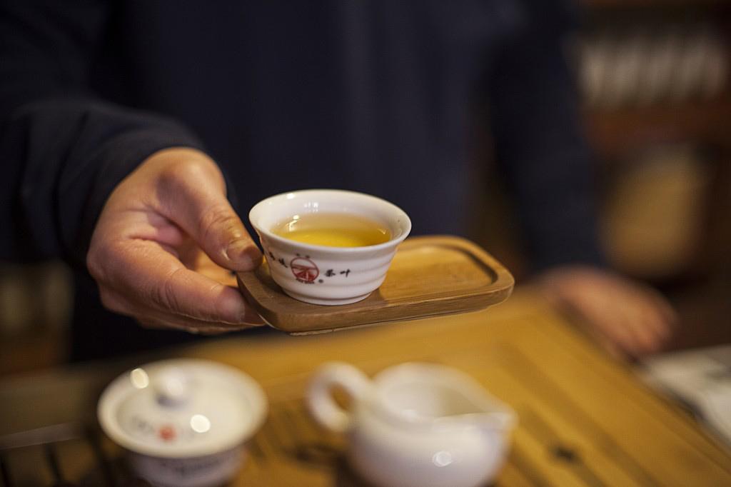 Herbata turkusowa oolong Yu Lan Xiang podawana w czarce herbaty na tradycyjnych chińskich podstawkach herbacianych.