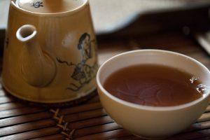 Herbata oolong Da Hong Pao w czarce i czajniczku z klasycznymi chińskimi zdobieniami.