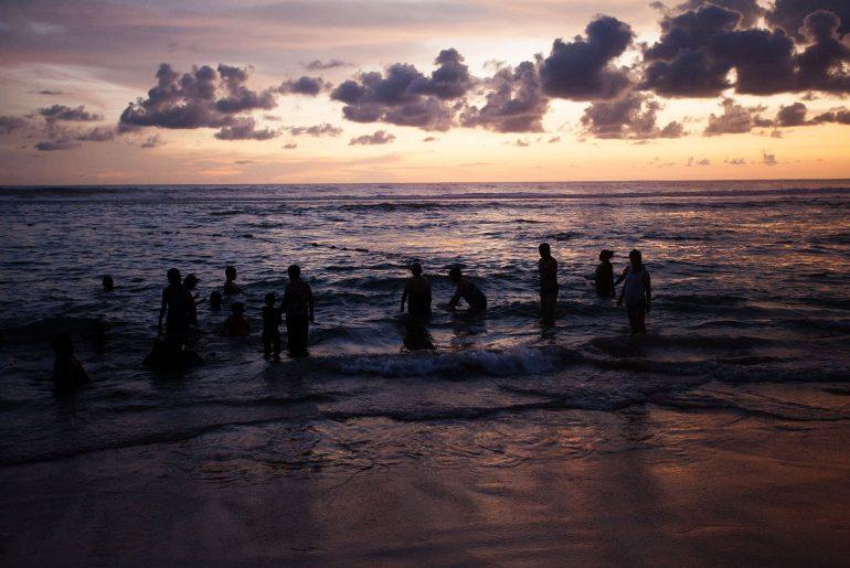 Kąpiący się w morzu ludzie na Sri Lance o zachodzie słońca