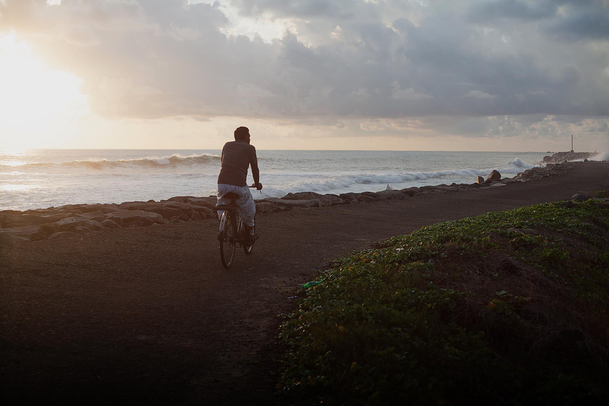 Rowerzysta na falochronie i zachód słońca na Sri Lance