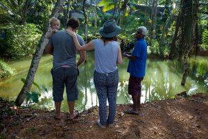 Para nowozelandczyków z synem karmi rybki podczas rozmowy z lankijskim producentem herbaty.