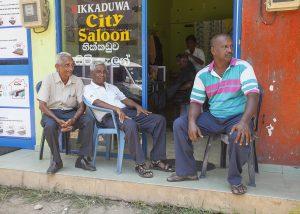 Mężczyźni przed salonem fryjerskim na Sri Lance odpoczywają w cieniu.