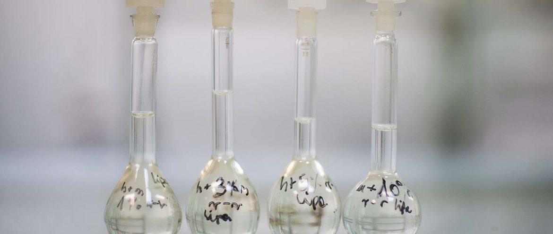 menzurki w laboratorium z roztworem herbaty z miodem