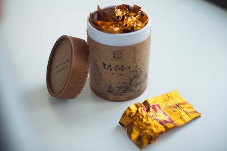 Otwarte, kartonowe opakowanie herbaty milk oolong i hermetycznie zamknięta saszetka z herbatą od Arti Unici, Red Seal Tea