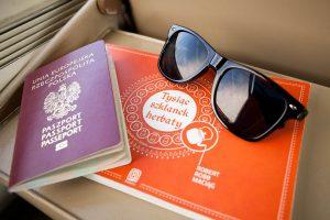 Paszport, książka o herbacie i okulary przeciwsłoneczne przydają się w podróży.