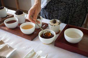 Testowanie herbaty poprzez siorbanie naparu z łyżki degustacyjnej
