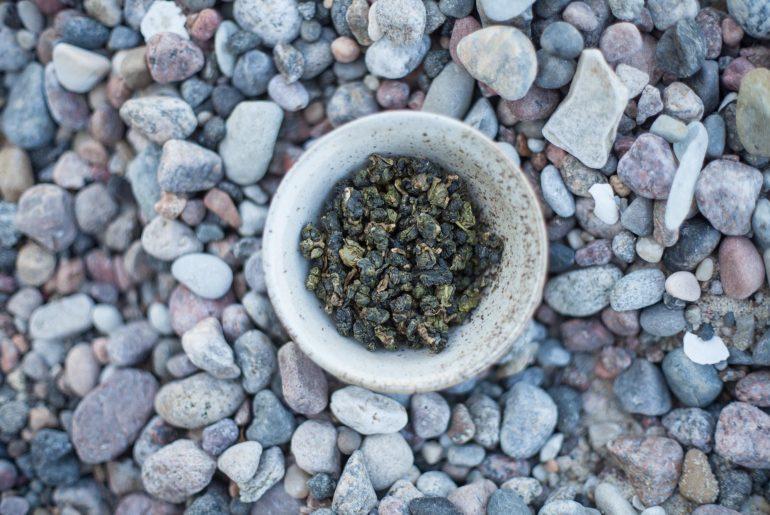Suche liście herbaty oolong w czarce służącej do picia herbaty, na kamienistym podłożu
