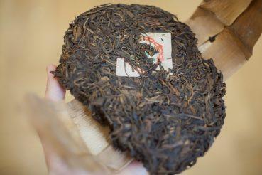 herbata pu erh zbita w ciastko oraz zapakowana w bambus, wraz z kartką z informacjami o herbacie pu erh