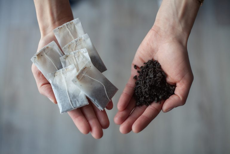 Dłonie na których dla porównania pokazano herbatę sypaną - herbatę liściastą oraz herbatę ekspresową, w saszetkach.