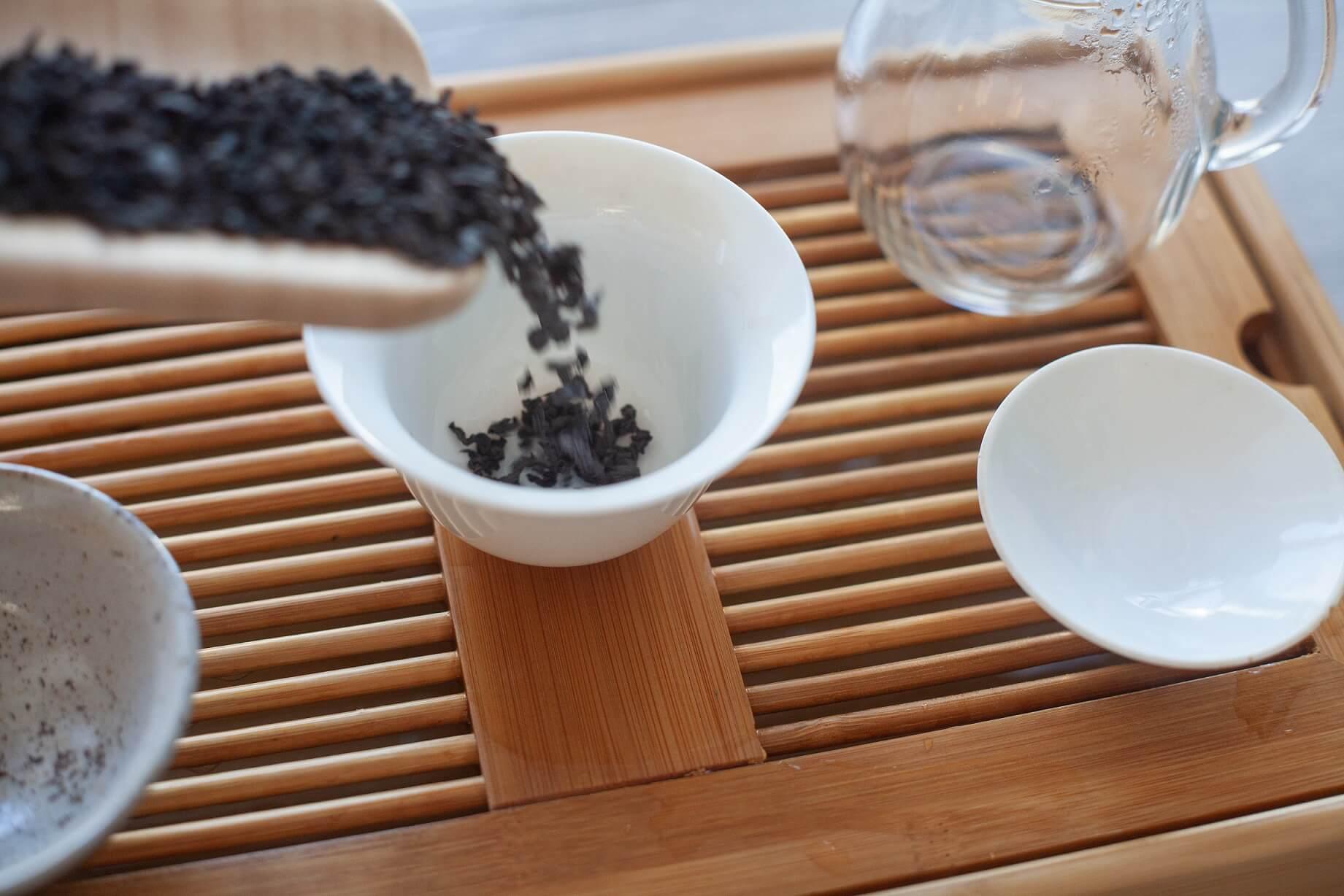 Naczynia do parzenia herbaty umieszczone na podstawce chapan, w tym gaiwan, do którego wsypywana jest z góry herbata czerwona.