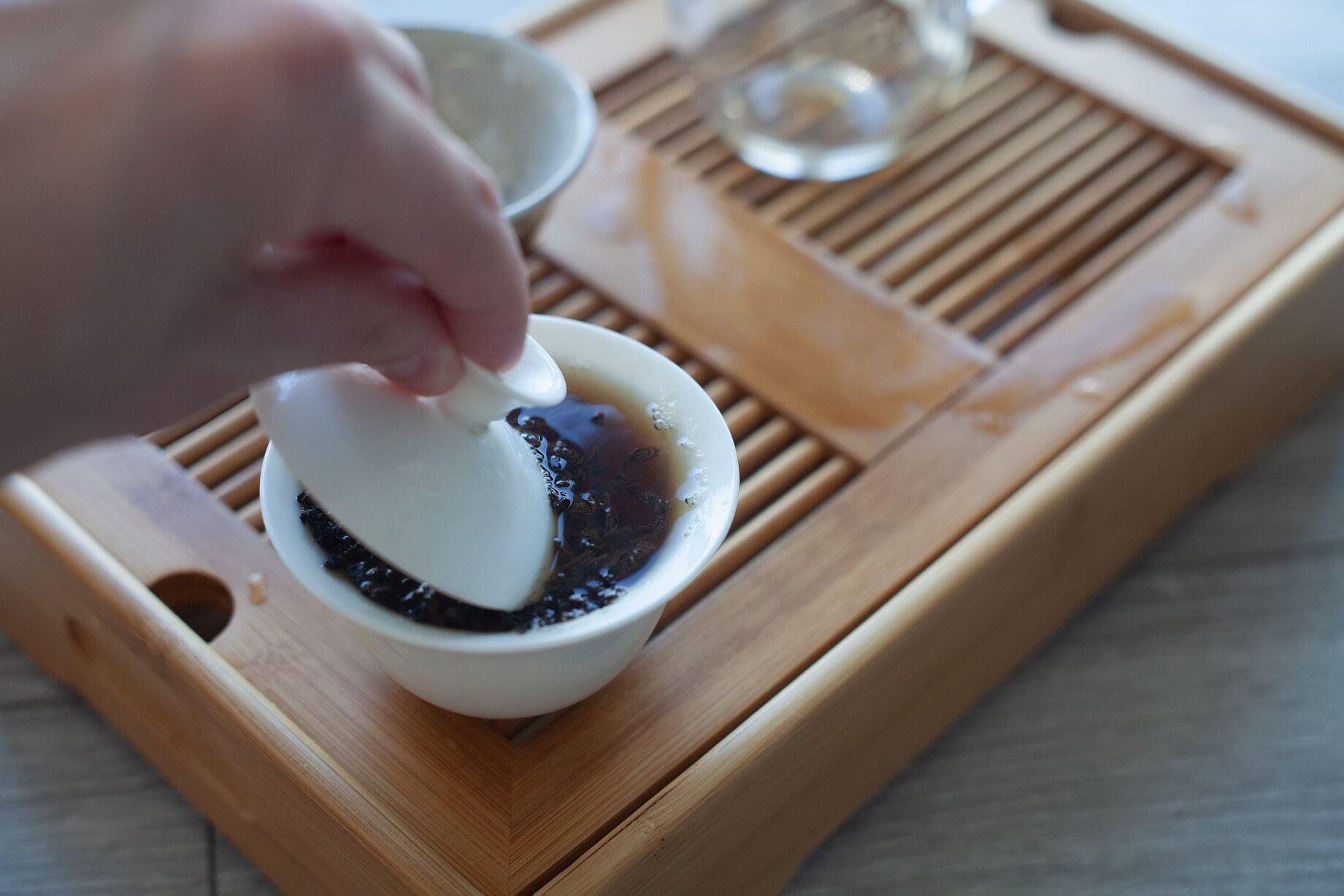 Zalany wrzątkiem gaiwan z suszem czerwonej herbaty w środku oraz zanurzonym delikatnie spodkiem gaiwana. Naczynie umieszczone na tacy do parzenia herbaty.